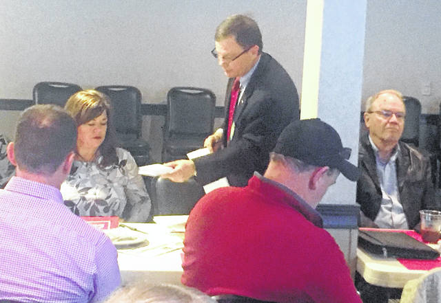 Hillsboro Rotarian Rocky Coss is shown at Tuesday's Rotary meeting in Hillsboro handing out pledge cards and discussing last minute details for Wednesday night's annual radio-telethon.