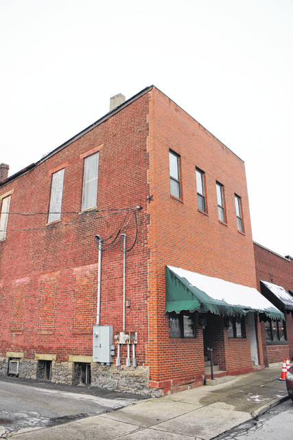 The demolition of a building on Gov. Foraker Place owned by Mayor Drew Hastings is being in limbo over questions raised by City Auditor Gary Lewis.