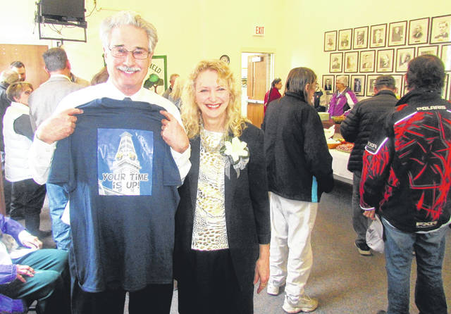 "Ron Coffey and his wife, Dianna, pose for a picture Friday at a farewell open house as Coffey holds up a t-shirt with a picture of the clock atop the Greenfield city building featuring his face in the clock tower with the caption, ""Your time is up!"""