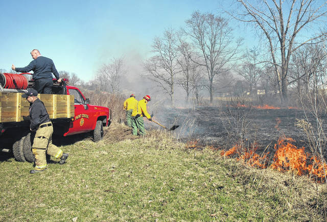 Firefighters work to extinguish a field fire Tuesday at a property on U.S. Route 50 near Hoagland. The fire was reportedly caused by a burning couch.