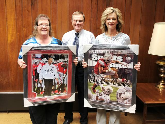 Merchants Bank representatives Bertha Hamilton, left, and Denise Fauber, right, present auction photographs to Rocky Coss, the Rotary Club radio-telethon chairman.