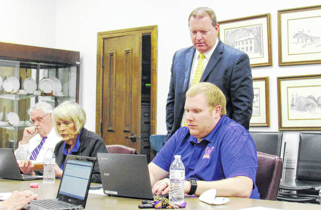Greenfield Superintendent Joe Wills, standing, guides board members through a new online process to access policy revisions at Monday's school board meeting. Also pictured are, from left, district Treasurer Joe Smith and board members Marilyn Mitchell and Charley Roman.
