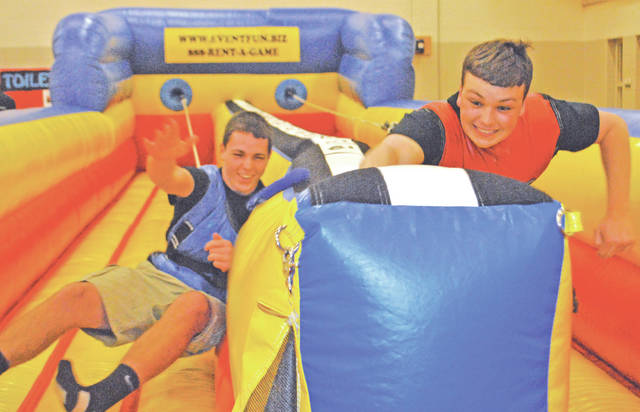 Hillsboro High School students Will Kiefer, right, and Brice Ertel participate in a bungee cord game Sunday morning at the Hillsboro After Prom Party.