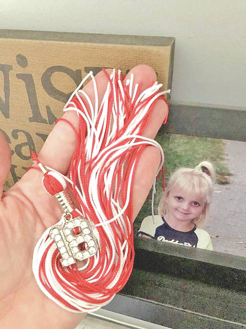 With her late daughter's picture in the background, Andi Reno holds a tassle that Anna Reno would have worn to her graduation next month.