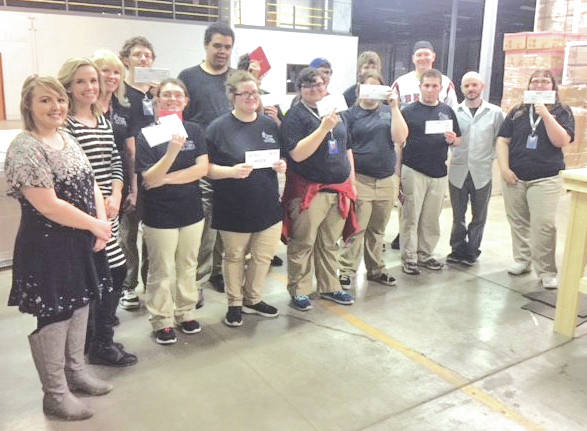 CareerX students at Laurel Oaks show off their first paychecks as Oaks staff members stand with them.