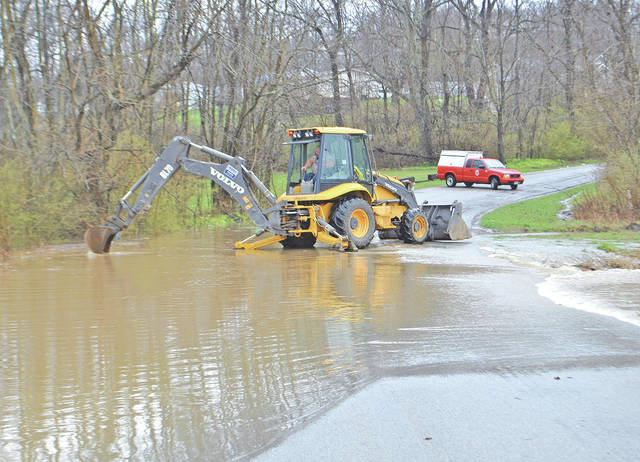 City of Hillsboro employee Aaron Milburn works to clear a culvert along North East Street around 11:30 a.m. Tuesday. The street was closed part of the day due to water running over it.