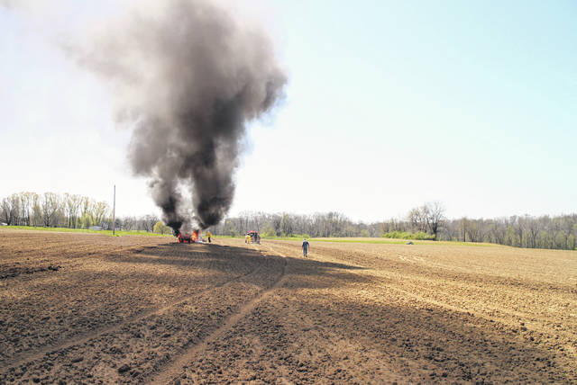A plume of smoke rises from a burning tractor Monday at a farm on Hill Road.