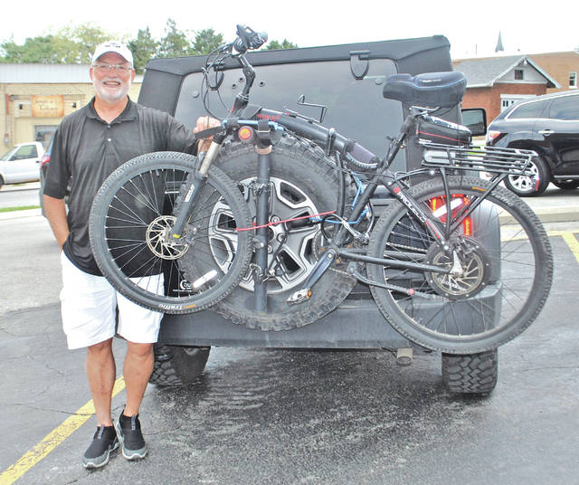 Ernie Vecchio is pictured behind The Times-Gazette offices Monday with his bike and jeep.