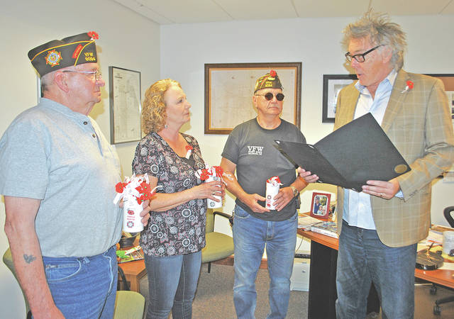 Hillsboro Mayor Drew Hastings is pictured Wednesday reading a proclamation declaring May 5-12 as Buddy Poppy Week in Hillsboro. The poppies shown in the picture can be purchased at the Hillsboro VFW, Hillsboro City Building and Highland County Veterans Service Office for a donation. Some of the proceeds benefit the disabled veterans who assemble the poppies, but a larger portion stays in Highland County to help local veterans. Pictured, from left, are John Walker, Hillsboro VFW poppy chairman; Kathy Murphy, VFW Auxiliary member; Dwight Reynolds, VFW senior vice commander; and Hastings.