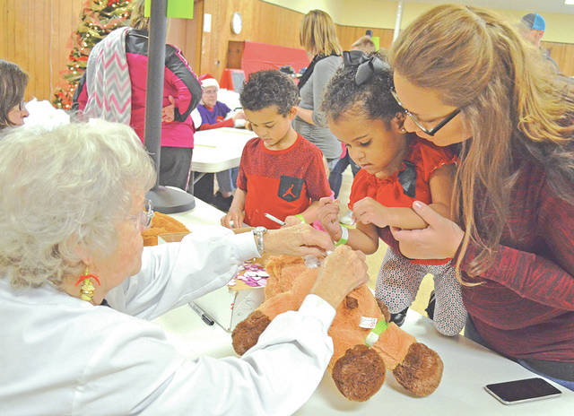 "Marsha Louderback, left, a volunteer with Samaritan Outreach Services, helps some visitors ""Build-A-Buddy"" at a past event."