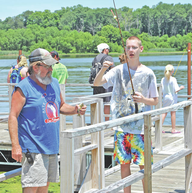 A KAMP Dovetail staff member, left, and camper are pictured with a prized catch during a past Dovetail event, while others fish in the background at Rocky Fork State Park.