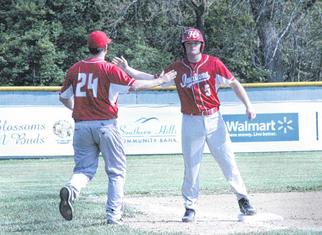 Hillsboro head coach Matt Garman (left) and Hillsboro senior Kelton Anderson give one another a high five following Anderson's one run triple in the bottom of the first inning Monday at Shaffer Park in Hillsboro where the Indians hosted New Lexington.