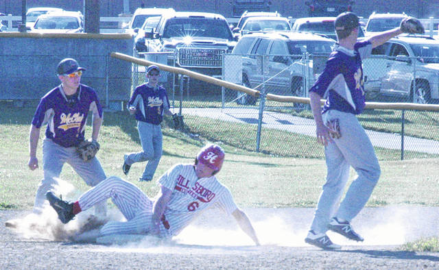 Hillsboro senior Kelton Anderson slides safely into second base after being caught in a pickle between first and second. McClain's Austin Booth (left) and Garrison Banks (far right) were unable to record the putout.