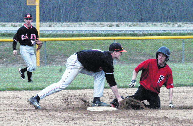 In this file photo, from April 27, Whiteoak's Mason Lehr tags Fairfield's Austin Setty at Fairfield High School as he slides into second base. In the background Wildcat Chase Butler moves toward the infield.
