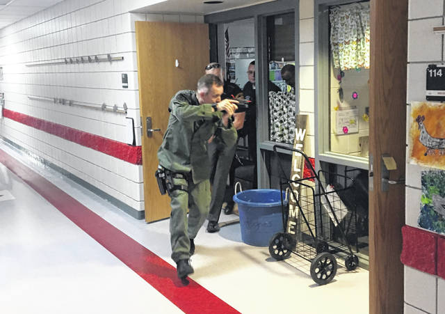 Sgt. Scott Cooper of the Highland County Sheriff's Office makes his way through a local school during a training exercise on Saturday.
