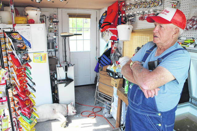 Ed Tipton leans against the minnow tank at his floating bait shop on Rocky Fork Lake Friday morning. Shown in the background is his dog, Sadie, napping on the floor.