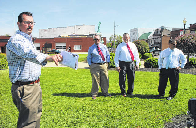 Hillsboro Safety and Service Director Mel McKenzie, left, gestures toward the portion of the Highland County Courthouse square that may soon be home to a decorative fountain. Also shown, from left, are Highland County Commissioners Jeff Duncan, Terry Britton and Shane Wilkin.