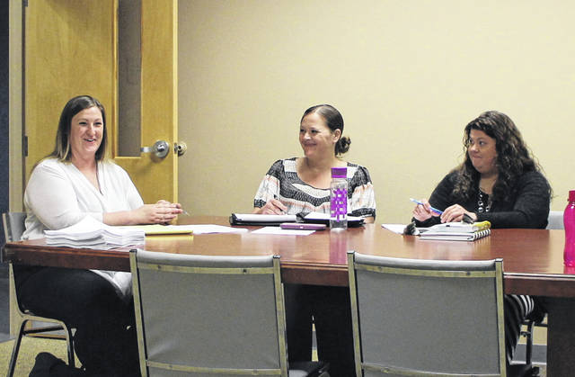 From left, Highland County Drug Abuse Prevention Coalition members Danielle Poe, Gena Bates and Monica Baucher share a chuckle at the coalition's monthly meeting on Thursday.