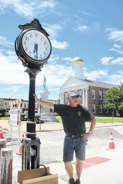 Sean Wooton of The Verdin Company, a Cincinnati firm specializing in the manufacture of clocks and bells, leans on a new decorative clock at the corner of Gov. Trimble Place and North High Street in uptown Hillsboro Monday.