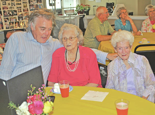Hillsboro Mayor Drew Hastings visits with Mary West (center) and Helen Sprinkle during a celebration in honor of their 102nd and 100th birthdays, respectively, Tuesday at Bell Gardens Assisted Living.