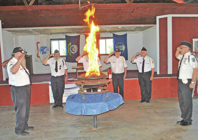 Highland County Veterans Honor Guard members, including Gerald Wilkin, left, and Scott Carrozza, right, stand in salute until a flag is burned in its entirety during a Flag Day flag retirement ceremony held Thursday at AMVETS of Hillsboro Post 61.