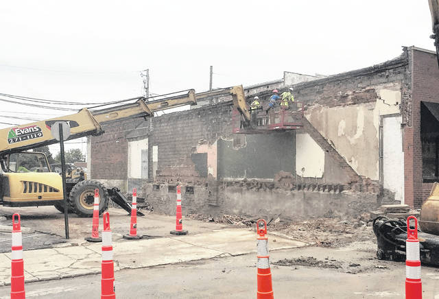 Workers are shown Monday taking down by hand the remaining wall of the former Armintrout building that was mostly demolished last week. The demolition project is expected to wrap up by Wednesday with the filling-in of the building's basement.