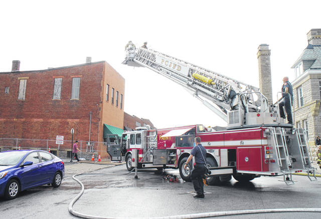 Emergency workers with Paint Creek Joint EMS/Fire District use a ladder truck Wednesday morning to check out the roof of the Armintrout building on Gov. Trimble Place, where a piece of demolition equipment overheated and began to smoke.