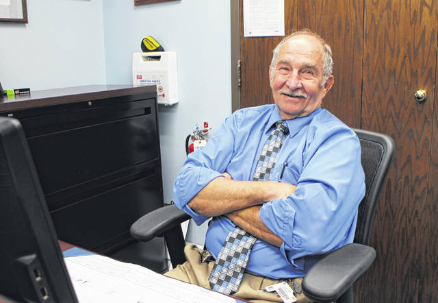 Bailiff Dan Music smiles behind the desk at the Highland County Common Pleas Court office. Music retires from his post on Friday.