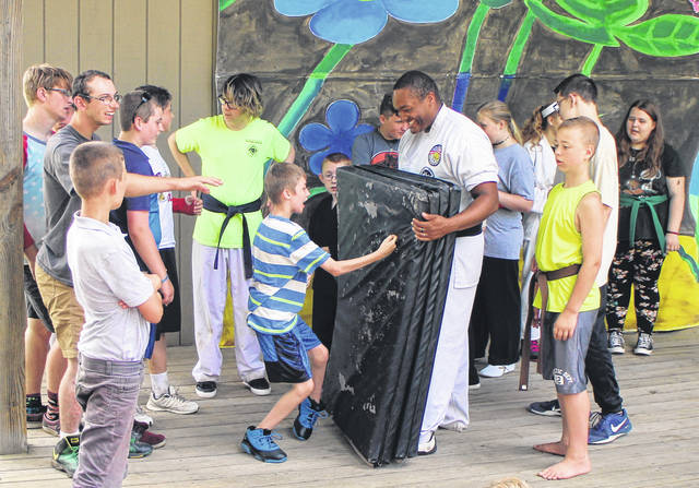 A happy camper takes a jab at a foam mat held by Erwin McIntosh III of 3G Karate at KAMP Dovetail Friday.