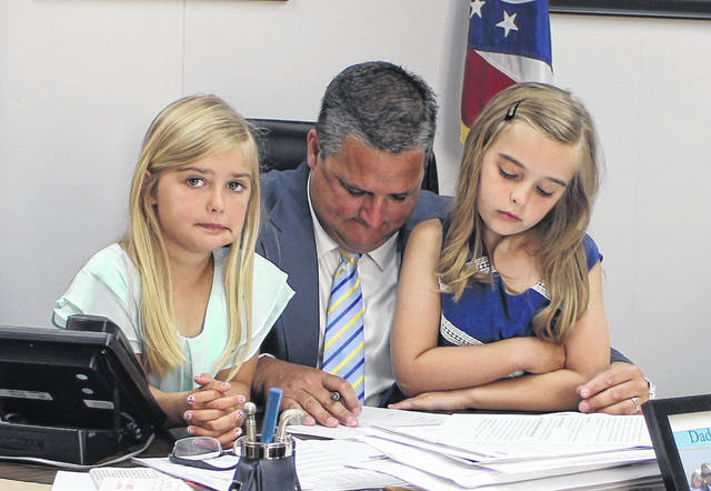 Shane Wilkin, center, attends his last meeting as a Highland County commissioner on Wednesday with his daughters, Parker, left, and Piper, right.