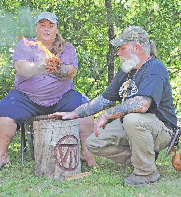 Tracy Wilson of The Woodsrunner School in South Carolina holds a starter bundle she lit using a bow drill Thursday afternoon at Rocky Fork State Park. Looking on is Dave Canterbury, organizer of the Pathfinder Gathering being held at the park campgrounds this weekend.