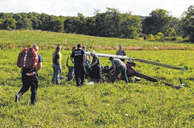 Paramedics approach the scene of an ultralight helicopter crash in the Fort Hill area Friday.