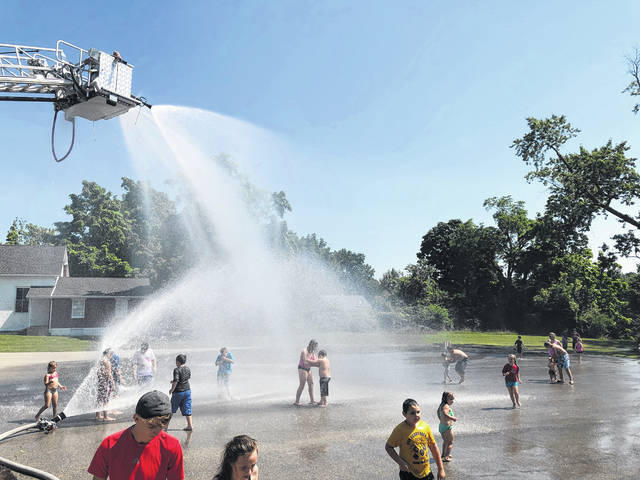 Paint Creek Joint EMS/Fire District's ladder truck sprays water on a crowd of kids Friday in the parking lot at the district's Hillsboro station.