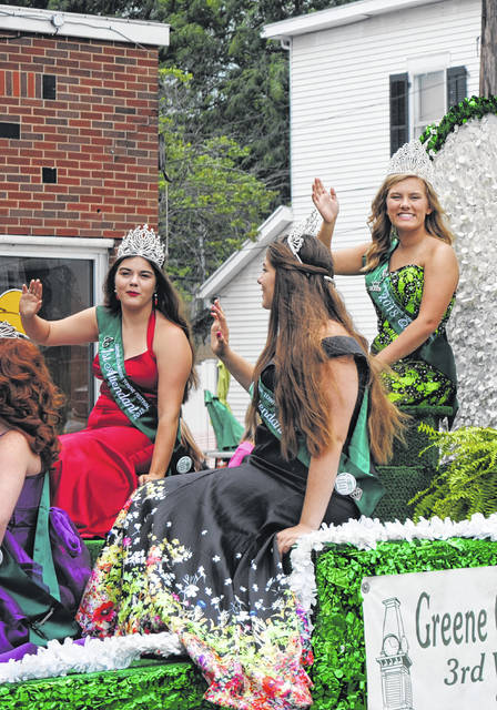 From left, first attendant Cheyenne Watson, second attendant Courtney Dodds and Greene Countrie Towne Festival Queen Katie Graham wave to paradegoers at the Greene Countrie Towne Festival in Greenfield Sunday.