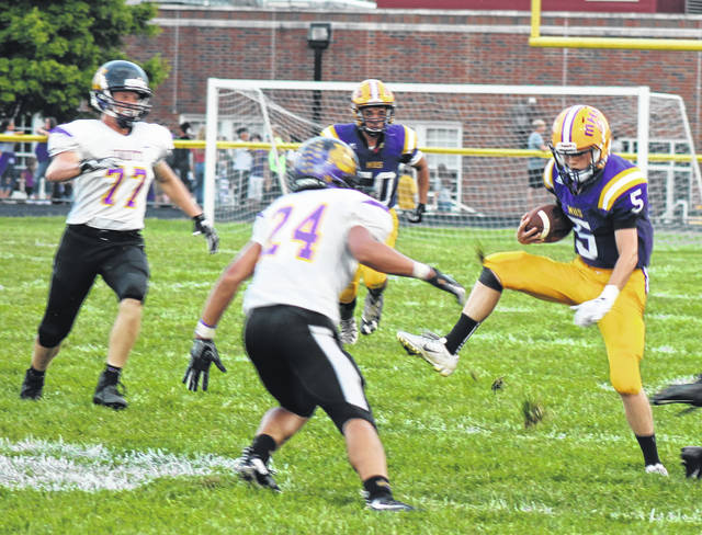 McClain quarterback David Jett jukes a Unioto defender on Friday at McClain High School where the Tigers took on the Shermans in high school football action.
