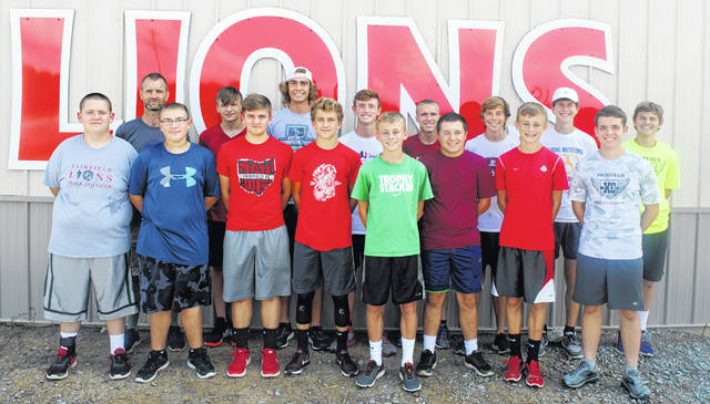 The Fairfield Lions varsity boys Cross Country team poses for a team photo in front of the home of the Lions sign at the Fairifeld track and field complex.