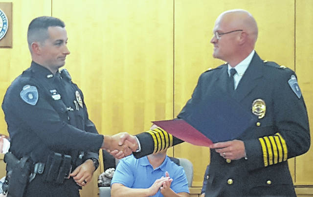 Hillsboro police officer Clint Sharp, left, receives a certificate of commendation from Hillsboro Police Chief Darrin Goudy at Monday night's city council meeting.