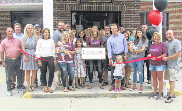 Dr. Dylan Hunter is pictured Friday cutting a grand opening ribbon with one his daughters, Evelyn, at Hunter Family Chiropractic, 219 W. Main St., Hillsboro. Pictured in front to the right are his wife, Jordan, and other daughter, Lucy, along his parents, Sue and John Hunter.