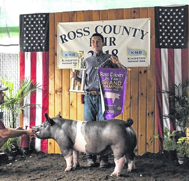 Garrett Simmons, a member of the Adena FFA group, is pictured with his County Market Hog Grand Champion at the 2018 Ross County Fair.