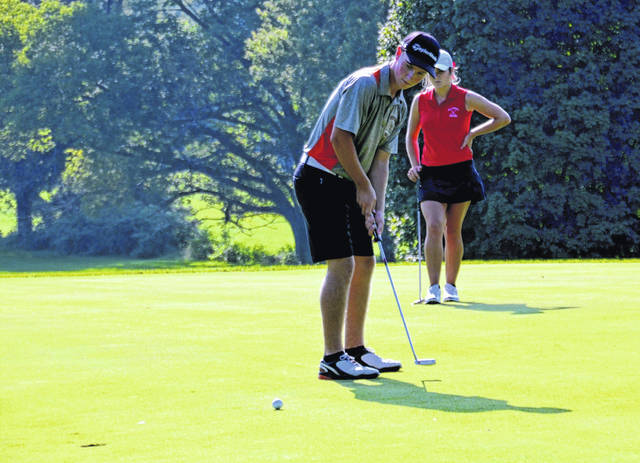 Whiteoak's Zach Harless putts as Hillsboro's Kristin Jamieson watches from behind on Monday at the Elks Golf Club in Hillsboro where the Indians took on the Wildcats in a cross-county golf rivalry.