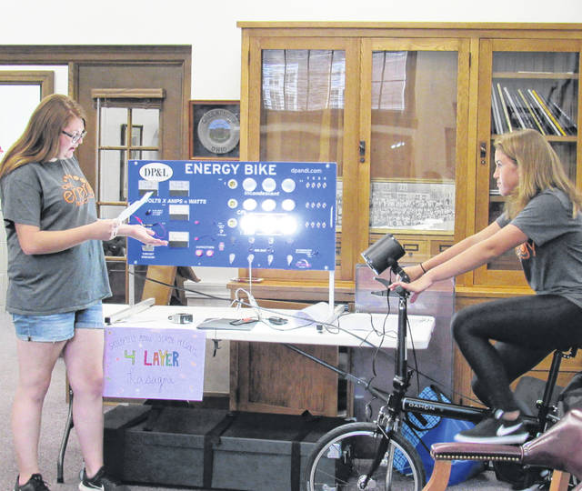 Middle school students Chloe Kirsch, left, and Shayna Beatty, seated on the bike, demonstrate to Greenfield school board members how their energy bike works, a project made possible by DP&L through a program geared toward fostering girls' interest in science.
