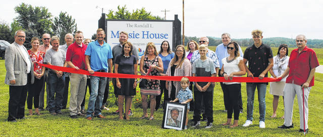 Past and present leadership of Family Recovery Services, Massie House staff, members of the Massie family and the Highland County Chamber of Commerce take part in Friday's ribbon cutting ceremony. Holding the scissors is Carol Massie, widow of the late Dr. Randall Massie.