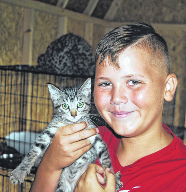 Twelve-year-old Nic Burns is shown holding one of the animals in need of adoption at the Highland County Humane Society Animal Shelter.