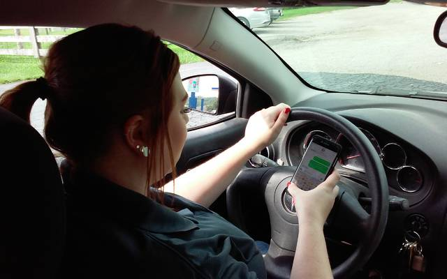Hillsboro resident Sami Hall show what not to do behind the wheel of a car.