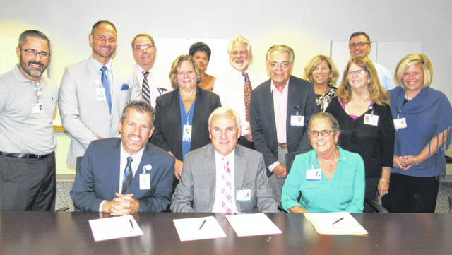Pictured are (seated., l-r) Fayette County Memorial Hospital CEO Mike Diener, Adena Health System President and CEO Jeff Graham, and Adena Board of Trustees Chair Virginia Wettersten signing an affiliation agreement between the two independent health care providers. Members of FCMH and Adena leadership teams also pictured.