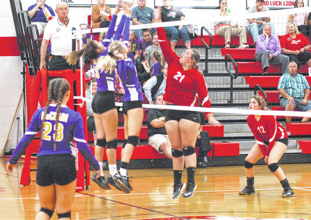 McClain's Taylor Butterbaugh (left) and Maddy Crawford (right) block an attempted spike by Fairfield's Taylor Lawson (21) while Lady Tiger Kaleigh Easter (23) and Lady Lion Kami Magee (12) are in position to follow up on the play.