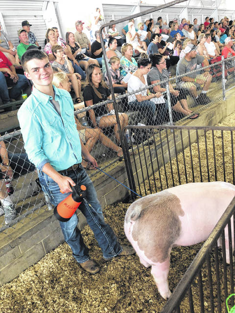 Hillsboro freshman Grant Miller is shown getting ready to enter the arena for a hog show.