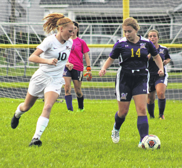 McClain's Aly Murphy dribbles up field as Miam Trace's Magarah Bloom defends Tuesday night.