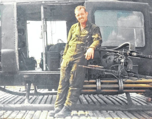 In South Vietnam, sometime in 1968, crew chief Navy Petty Officer 1st Class Ollie Gross takes a break from prepping his Huey helicopter for its next mission.