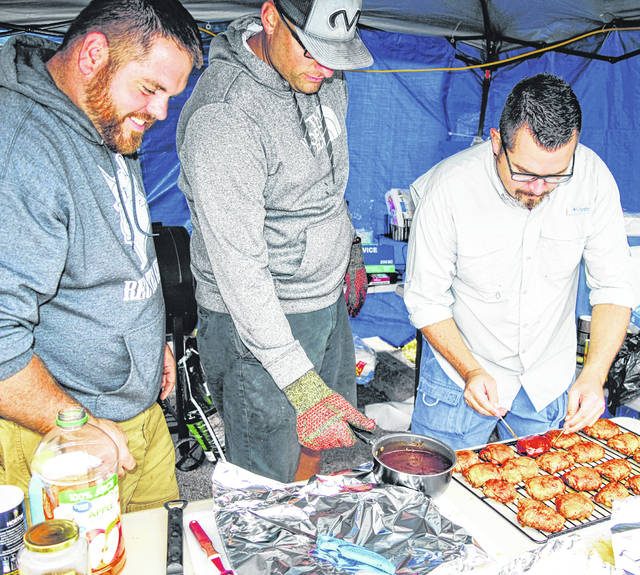 Local Four Guys and a Grill team members, from left, Jason McNeal, Jarrod Haines and Mel McKenzie prepare chicken during Saturday's Smokin' in the Hills Barbecue Contest.